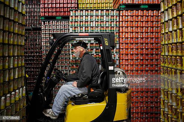 A forklift operator moves through stacks of empty aluminum soda cans at the Dr Pepper Snapple Group Inc bottling plant in Louisville Kentucky US on...