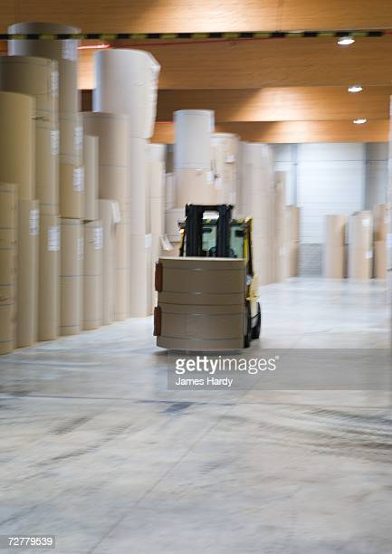 Forklift transporting roll of paper in warehouse