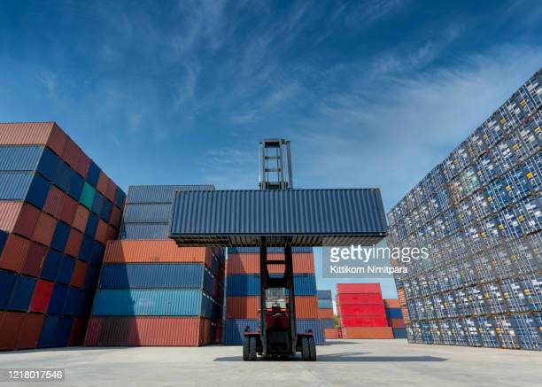 forklift truck lifting cargo container in shipping yard or dock yard against blue sky with cargo container stack in background for transportation import,export and logistic industrial concept - bay of water stock pictures, royalty-free photos & images