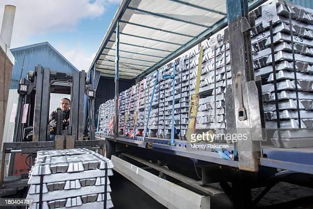 Forklift truck loading aluminium ingots onto truck for delivery