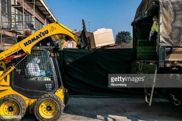 Forklift truck loads a coffin, containing a victim of coronavirus, from a re-purposed warehouse of a road maintenance company, onto a military truck...