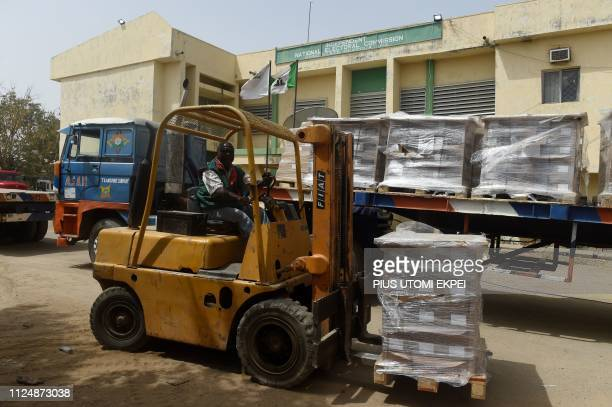 A forklift truck offloads electoral materials on a trailer at the headquarters of Independent National Electoral Commission in Kano Nigeria on...