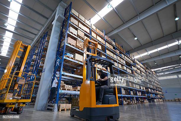 Forklifts carrying cardboard box in warehouse.