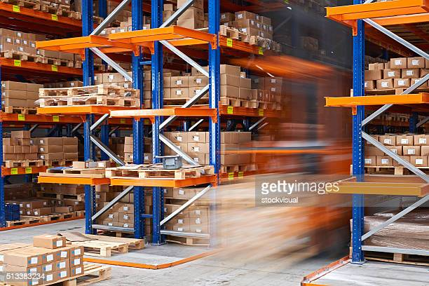 forklifts carrying cardboard box in warehouse. - storage compartment stock pictures, royalty-free photos & images