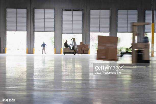 forklifts moving pallets in warehouse - loading dock stock pictures, royalty-free photos & images