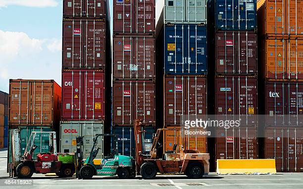 Forklifts sit in front of stacked shipping containers at the Port of Savannah in Savannah, Georgia, U.S., on Friday, Aug. 14, 2015. The trade deficit...