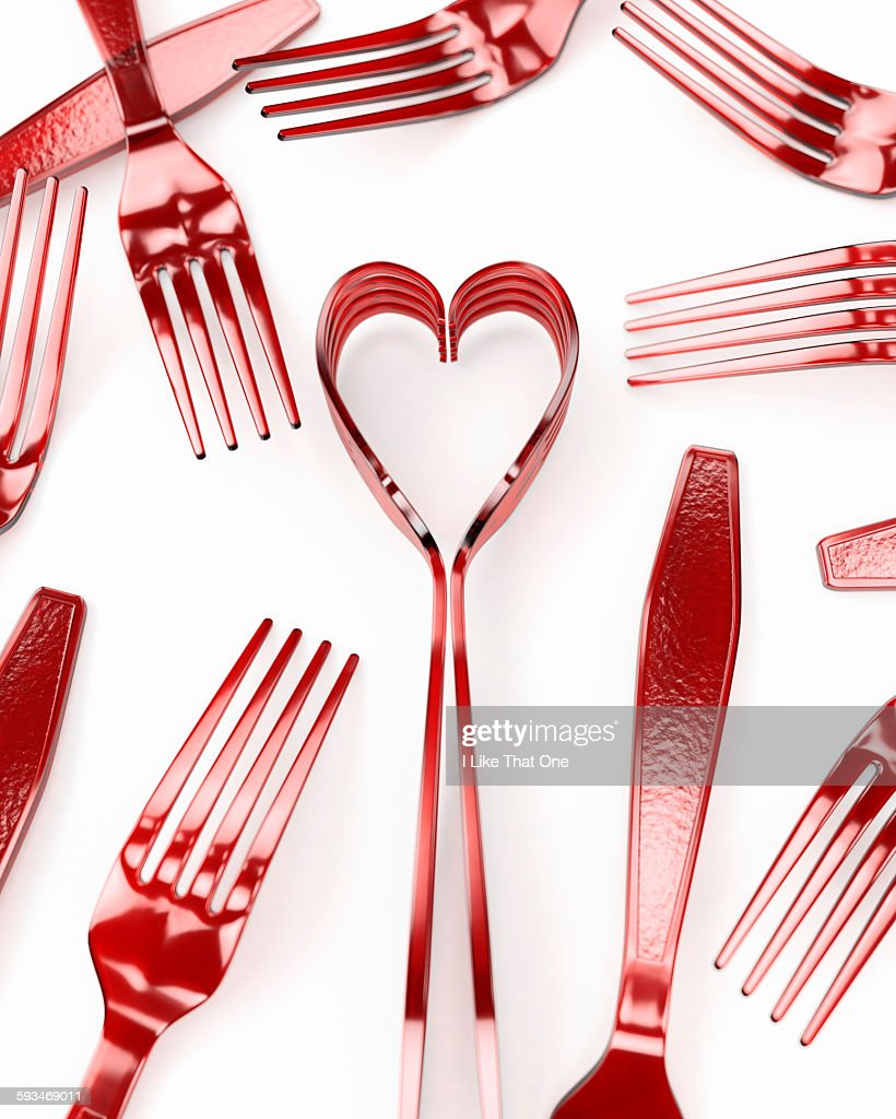 Forks on a white surface depicting a heart : Stock Photo