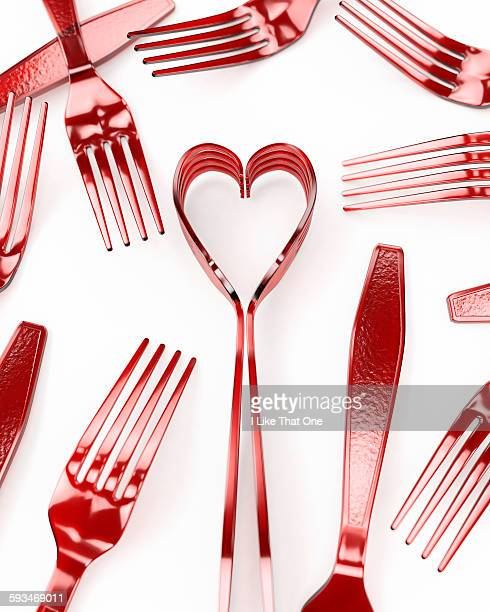 Forks on a white surface depicting a heart