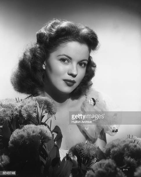 Formal headshot portrait of actor Shirley Temple wearing a low cut evening dress posing with flowers