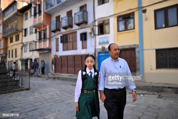 Formal Living Goddess Kumari MATINA SHAKYA in a school uniform along with her Father walks towards school on her first day at Kathmandu Nepal on...