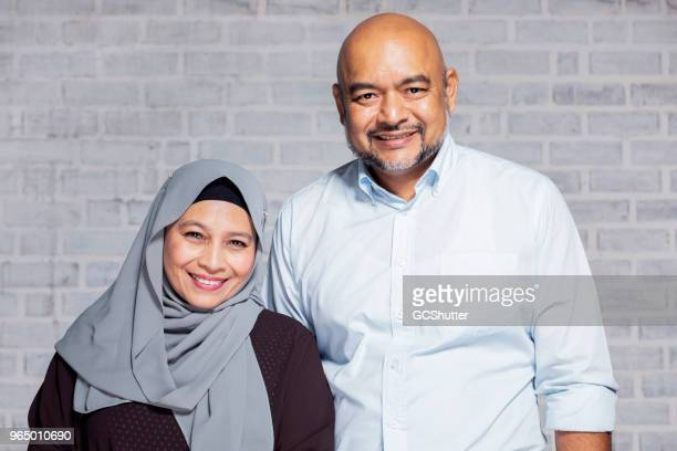 formal portrait of a senior malaysian couple - malaysian culture stock pictures, royalty-free photos & images