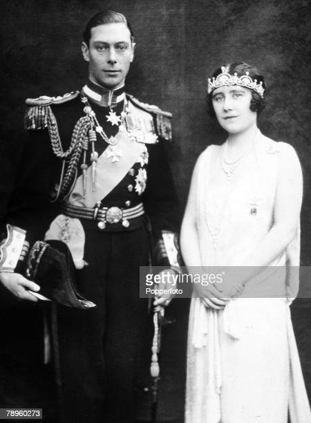 Formal portrait of King George VI wearing uniform as he stands with his wife Queen Elizabeth in 1928 when they were the Duke and Duchess of York