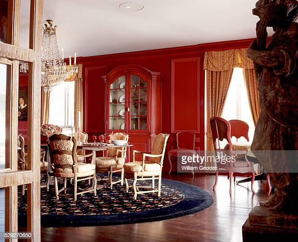 Formal red dining room with hardwood floor and crystal chandelier