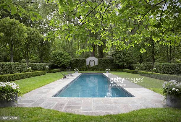 Formal shaped hedge garden with narrow pool