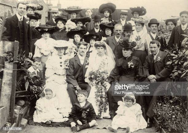 Formal wedding group shot, the bride wears a traditional white dress and veil and the groom wears a three piece suit with white collar, the male...