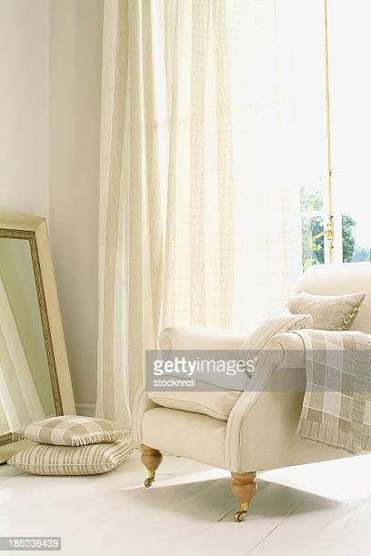 Formal white chair next to window with curtain