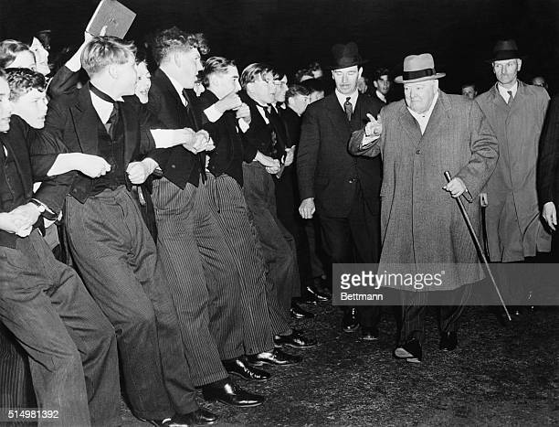 Formally clad Harrow students lock arms to keep their enthusiastic schoolmates from overwhelming Prime Minister Sir Winston Churchill as he paid a...