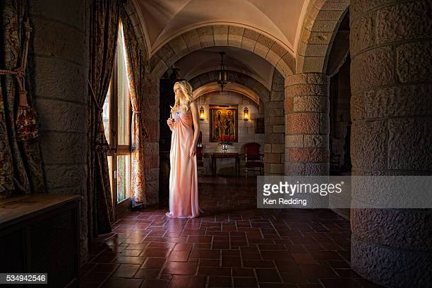 Formally dressed blonde woman standing in front of large window in entrance hall
