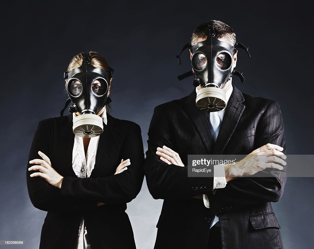 Formally dressed couple in gas masks fold arms and stare : Stock Photo