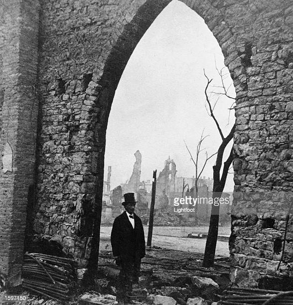 A formally dressed Black man stands in front of the stone arch of the Second Presbyterian Church through which can be seen the remains of the Tribune...