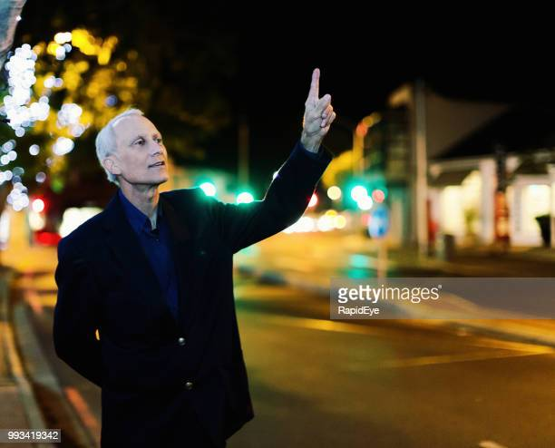 Formally dressed mature businessman hailing a cab in nighttime street