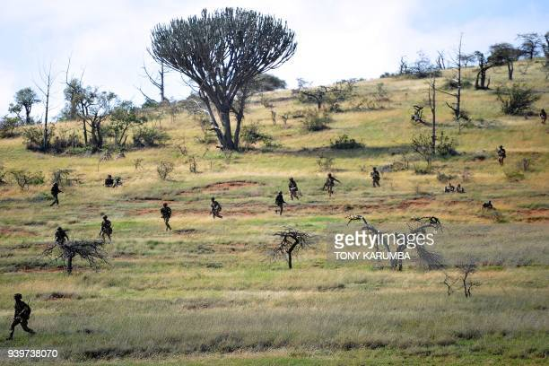 A formation of advancing soldiers scurry down a hill during a simulated military excercise of the British Army Training Unit in Kenya together with...