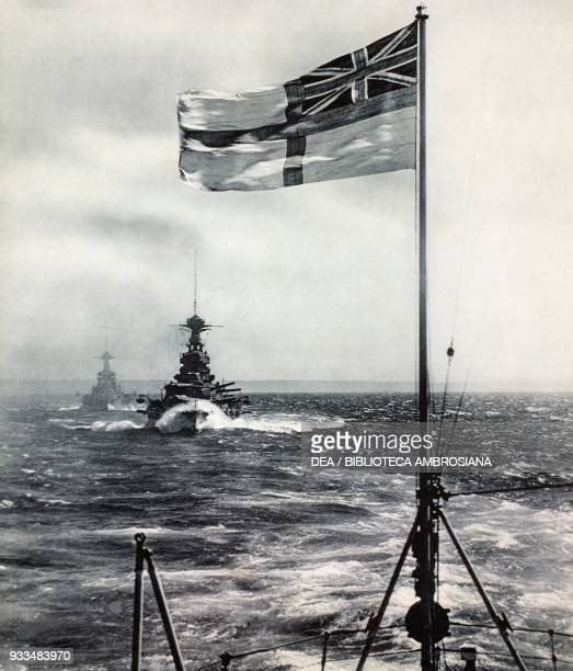 Formation of warships, the Royal Navy Ensign in the foreground, photograph from The Illustrated London News, July 20, 1935.