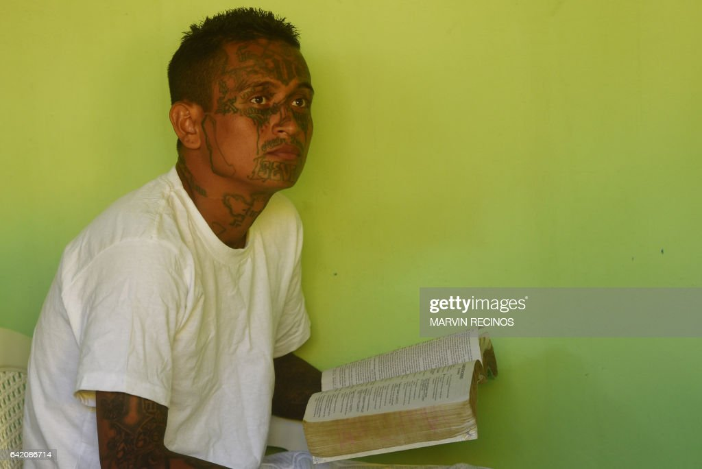 A former 18th Street gang member attends a class on biblical education at the San Francisco Gotera prison, 165 km from San Salvador, on February 16, 2017. In the San Francisco Gotera prison there are 1122 gang members, from whom more than 500 say having abandoned their gangs and feel sorry for their crimes. / AFP / Marvin RECINOS
