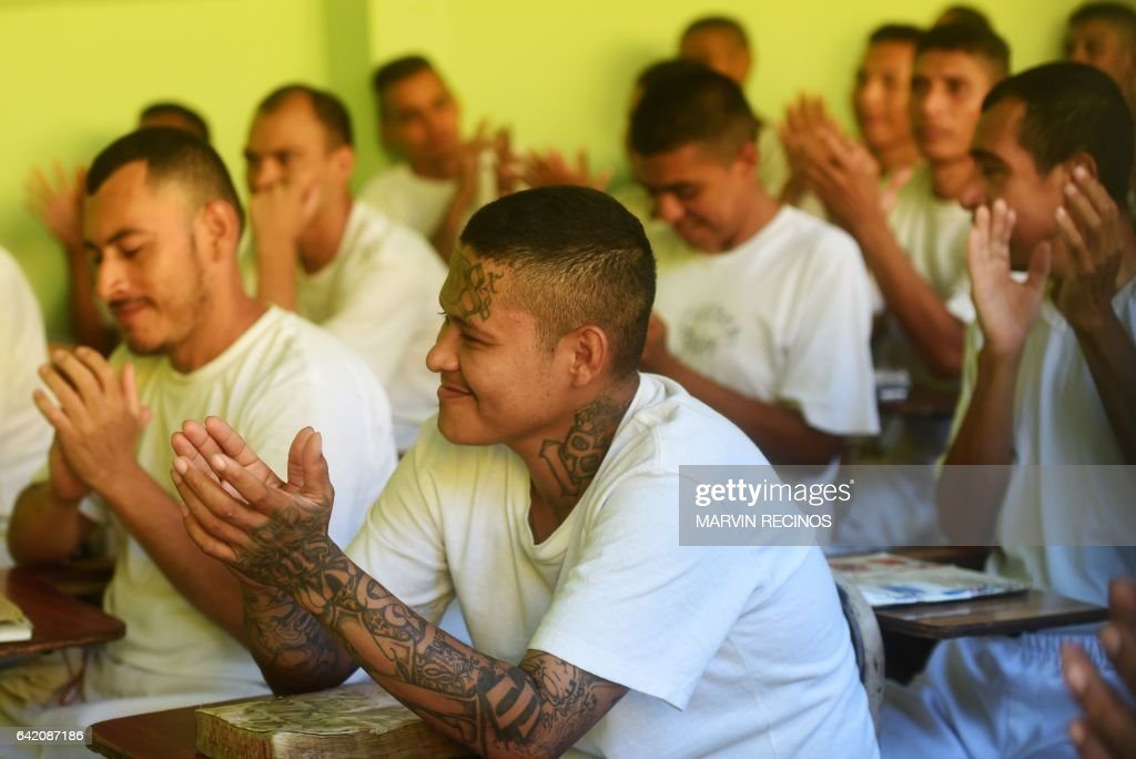 Former 18th Street gang members attend a class on biblical education at the San Francisco Gotera prison, 165 km from San Salvador, on February 16, 2017. In the San Francisco Gotera prison there are 1122 gang members, from whom more than 500 say having abandoned their gangs and feel sorry for their crimes. / AFP PHOTO / Marvin RECINOS