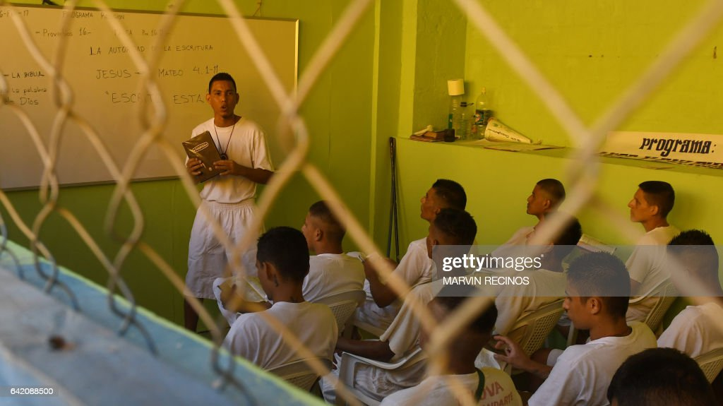 Former 18th Street gang members attend a class on biblical education at the San Francisco Gotera prison, 165 km from San Salvador, on February 16, 2017. In the San Francisco Gotera prison there are 1122 gang members, from whom more than 500 say having abandoned their gangs and feel sorry for their crimes. / AFP / Marvin RECINOS