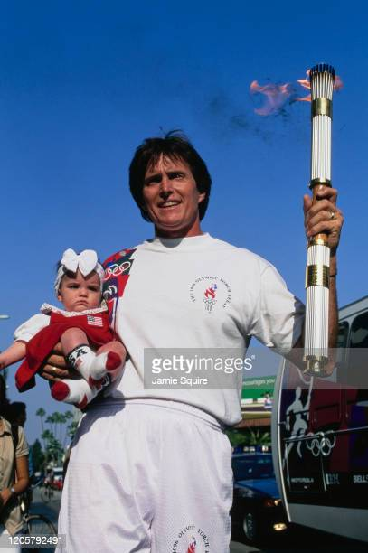 Former 1976 Olympic Decathlon gold medallist Bruce Jenner holds the Olympic Torch with daughter Kendall Jenner during the torch relay for the XXVI...