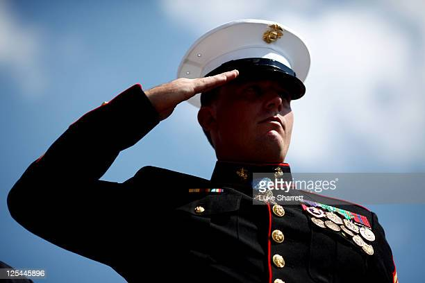 Former active duty Marine Corps Corporal and Medal of Honor recipient Dakota Meyer salutes during the playing of the national anthem after leading...