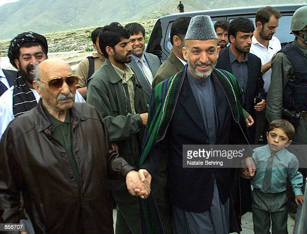 Former Afghan King Zahir Shah holds the hand of Interim leader Hamid Karzai as Karzai holds hands with Ahmed Agha the son of Kandahar governor Gul...