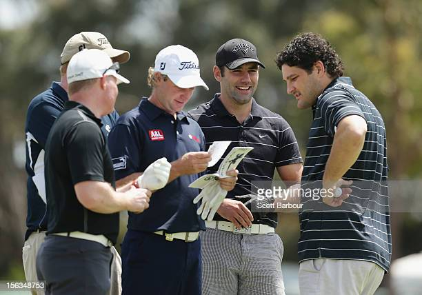 Former AFL footballer Brendan Fevola and rugby league player Cameron Smith stand with Peter Wilson of Australia during the Pro-Am Day ahead of the...