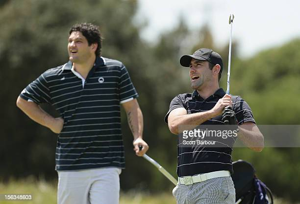Former AFL footballer Brendan Fevola watches as rugby league player Cameron Smith hits an approach shot during the Pro-Am Day ahead of the 2012...