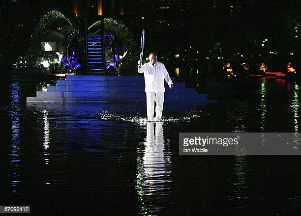 Former AFL footballer Ron Barassi carries the Queen's Baton across the Yarra River on the way to the Melbourne Cricket Ground for the opening...