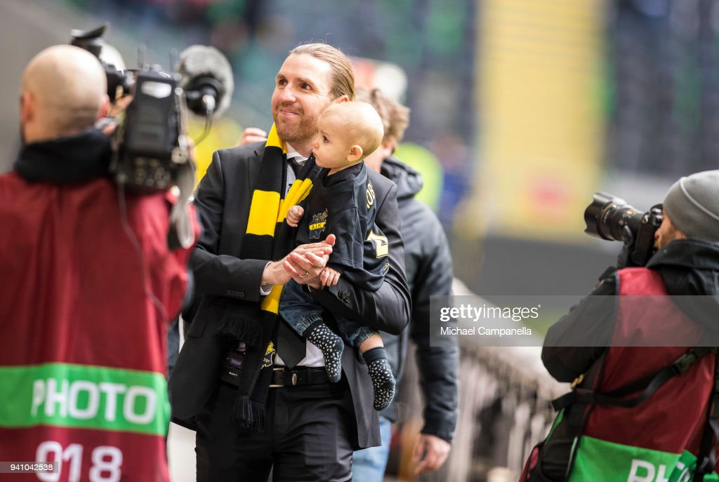 Former AIK captain Nils-Eric Johansson takes a lap of honor while holding his son before an Allsvenskan match between AIK and Dalkurd FF at Friends arena on April 2, 2018 in Solna, Sweden. Nils-Eric Johansson, who has been with AIK for 10 years was forced to retire because of a heart condition.