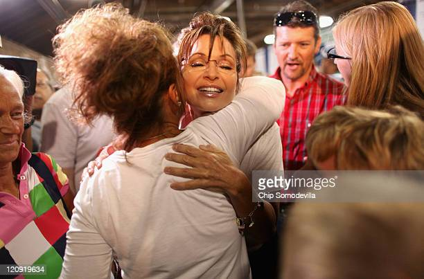 Former Alaska Governor Sarah Palin embraces a fairgoer while visiting the Cattle Barn at the Iowa State Fair August 12 2011 in Des Moines Iowa...