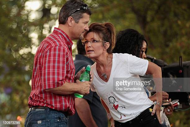 Former Alaska Governor Sarah Palin talks with her husband Todd Palin before appearing on the Sean Hannity Show during the Iowa State Fair August 12...