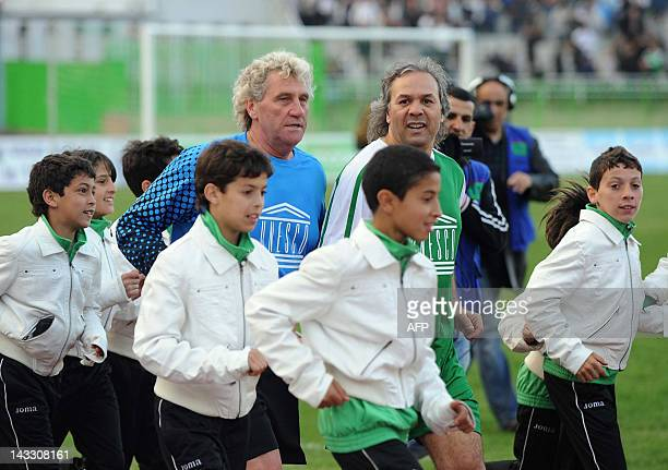 Former Algerian football star and UNESCO Goodwill Ambassador Rabah Madjer and Former Belgian goalkeeper JeanMarie Pfaff walk on the pitch amongst...