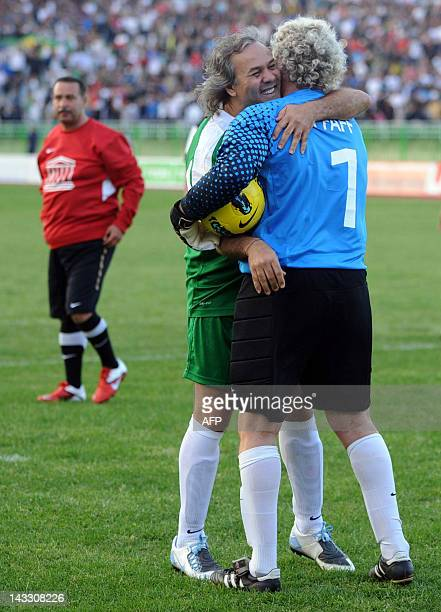 Former Algerian football star and UNESCO Goodwill Ambassador Rabah Madjer is embraced by Former Belgian goalkeeper JeanMarie Pfaff as they take part...