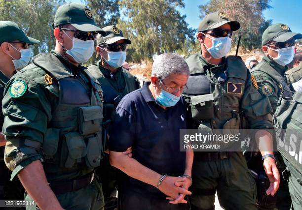 Former Algerian prime minister Ahmed Ouyahia, who is serving a 15 years prison sentence for corruption, is escorted by police as he attends the...