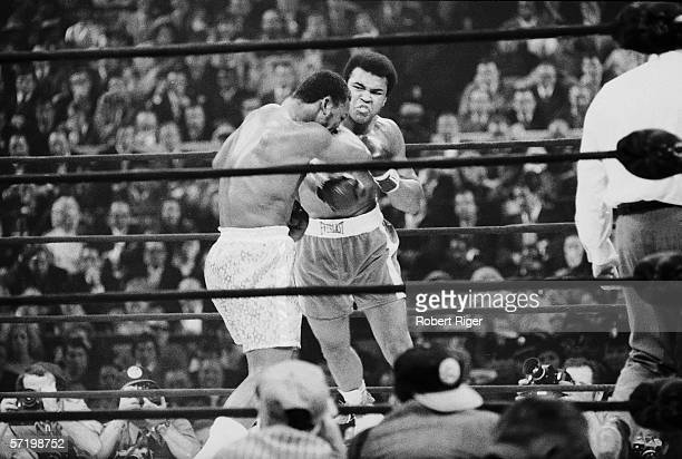 Former American heavyweight boxing champion Muhammad Ali delivers a punch to current champion Joe Frazier's head during their 'Fight of the Century'...