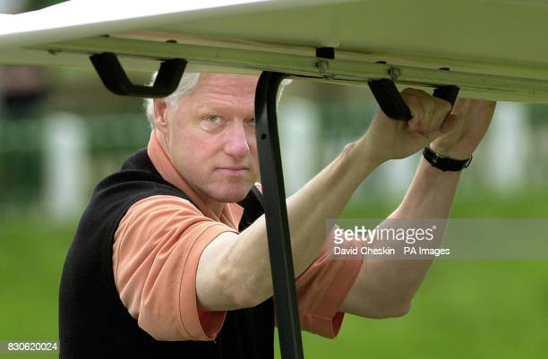 Former American President Bill Clinton holds onto the handle of a golf buggy as he arrives at the Old Course at the Royal and Ancient Golf Club in St...