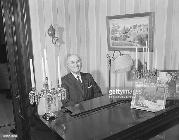 Former American president Harry Truman sits and smiles as he plays the piano in his home for an episode of the CBS celebrity interview program...