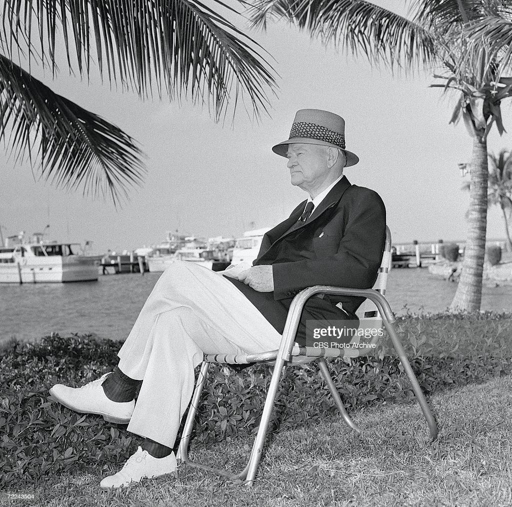 Former American president Herbert Hoover (1874 - 1964) weras a hat as he sits on a lawn chair and looks over the water outside his cottage for an episode of the CBS interview program 'Person to Person,' Key Largo, Florida, March 1960.