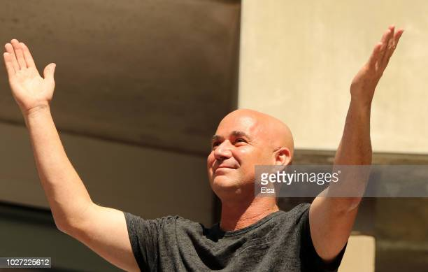 Former American tennis player Andre Agassi waves to fans during the men's singles quarterfinal between Kei Nishikori of Japan and Marin Cilic of...