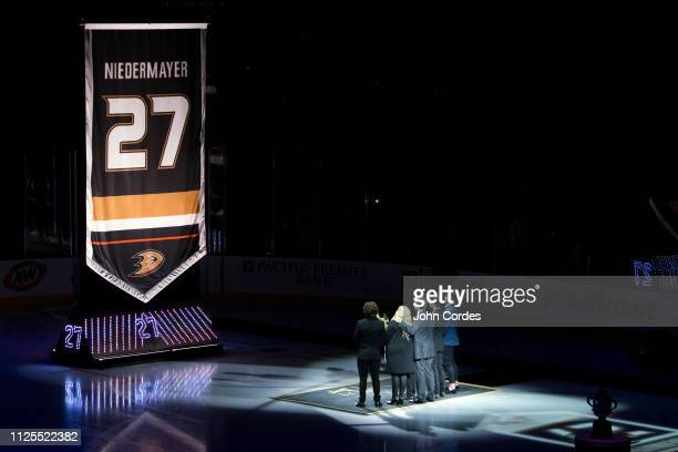 Former Anaheim Duck Scott Niedermayer watches his jersey rise to the rafters with his family during the jersey retirement ceremony prior to the game...
