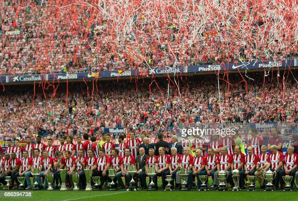 Former and current Club Atletico de Madrid players pose in front of their trophies at the end of the La Liga match between Club Atletico de Madrid...