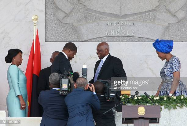 Former Angolan President Jose Eduardo dos Santos congratulates newly sworn in Angolan President Joao Lourenco during his swearing in ceremony as the...